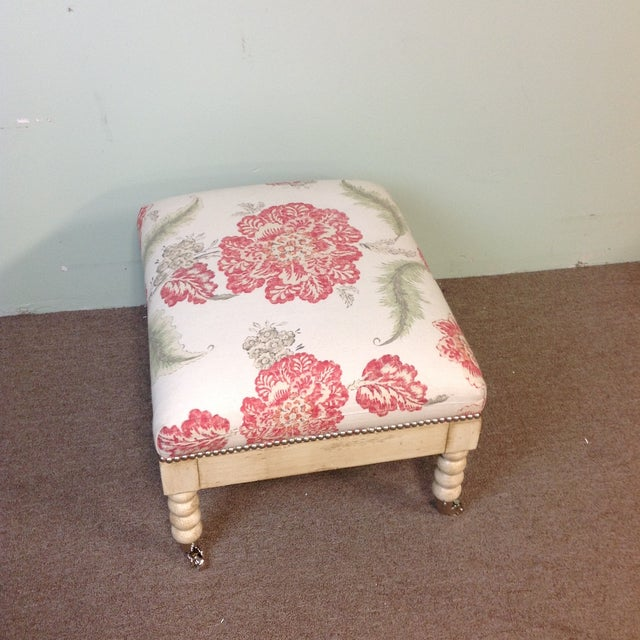 This Lillian August Ottoman has standard casters and nail heads give it an antique finish. The upholstered floral pattern...