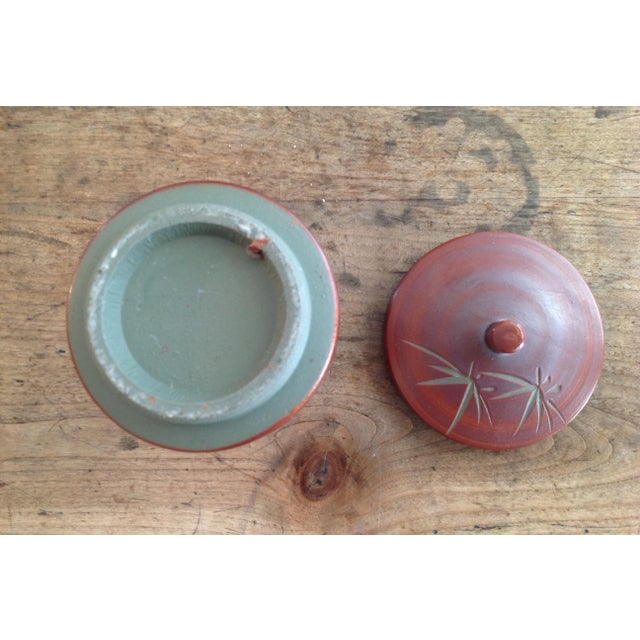 An exquisite small red - brown glazed stoneware pot with lid. Incised bamboo design in matte green. Lid has a button knob....