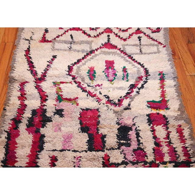 This striking Moroccan rug features strong geometric patterns and bold magenta details that create a variety of abstract...