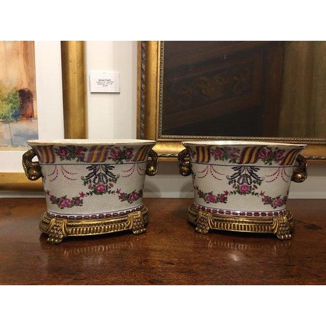 Pair of porcelain cache pots or jardinières with a floral motif, 20th century.