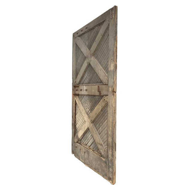 A monumental 19th century American barn door with two large X supports across the front, with diagonal painted beadboard...