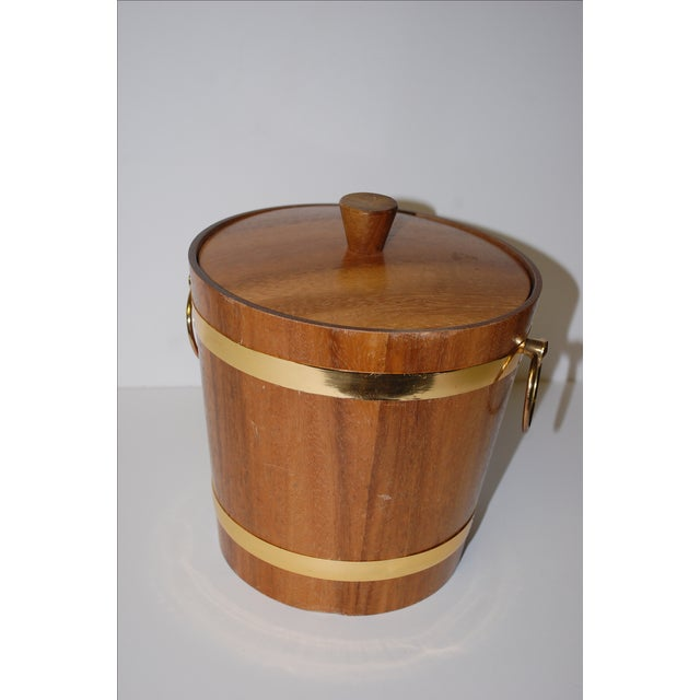 Great vintage 1950s aluminum lined teak ice bucket with brass handles and accents.