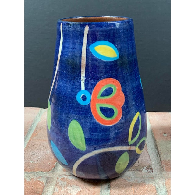 Hand painted terra cotta vase from El Salvador features brightly colored abstract leaves and flowers on a cobalt blue...
