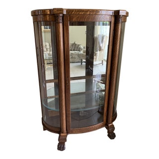 Antique Tiger Oak Curved Glass Mirrored Back Curio Cabinet on Claw Feet For Sale
