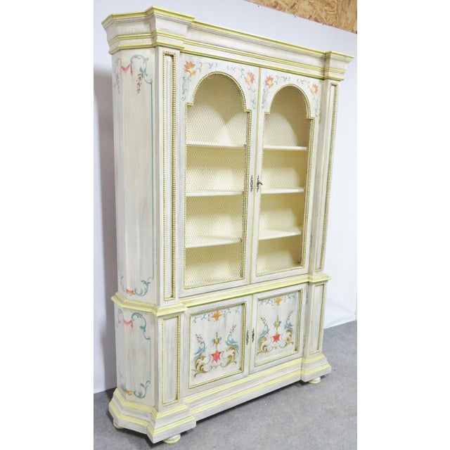 Cream painted with yellow highlights and floral and urn paint decoration. Top portion with two doors with chicken wire...