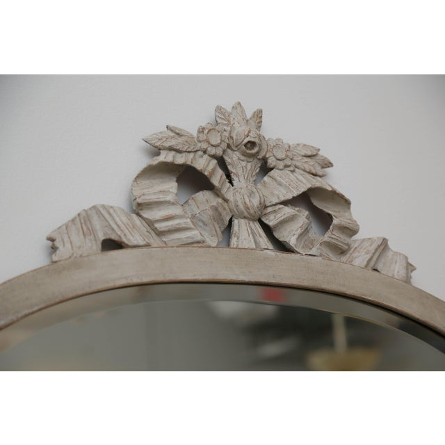 Antique Swedish Gustavian style oval mirror painted in distressed Swedish white/greyish finish, a lovely carved bow and...