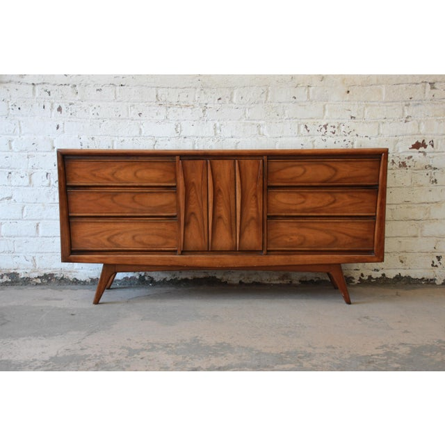 Offering a nice Mid-Century modern sculpted front dresser by United Furniture Co. The dresser features 9 drawers that...
