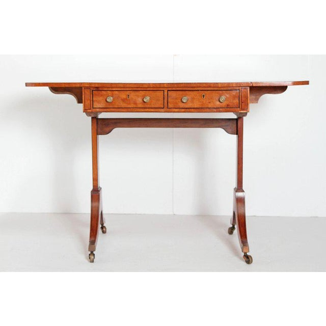 An English Regency satinwood drop leaf writing or side table. Nicely figured rectangular top with ebony stringing along...