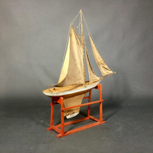 """Wonderful condition to this well-crafted pond sailboat. Hull made of painted metal and named at front """"Avis."""" The piece..."""