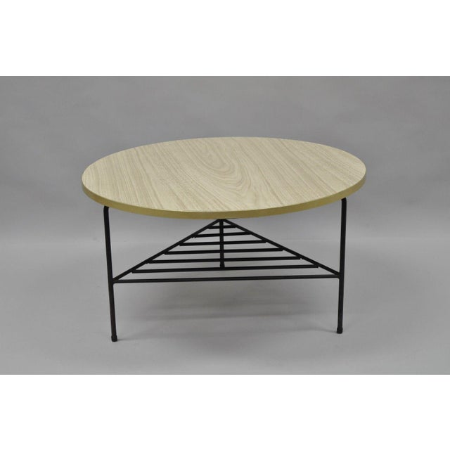 Tripod wrought iron base, lower shelf, round wood grain laminate top, brass tone metal band, sleek Atomic Modernist form....