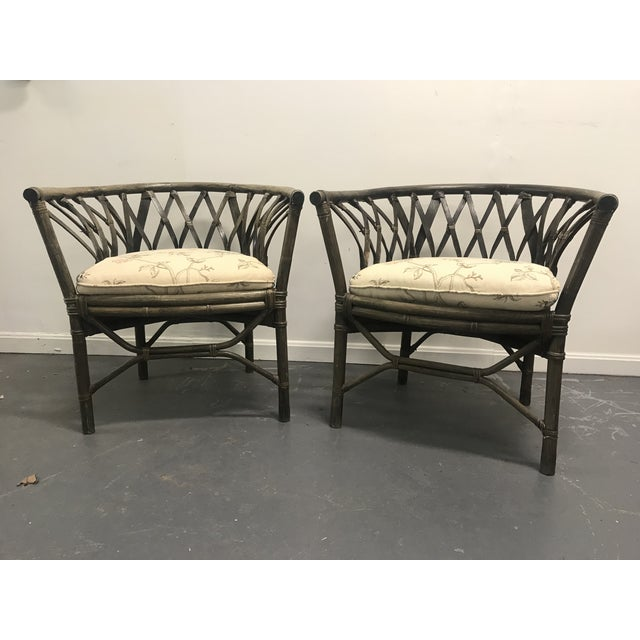 Beautifuly sloped back pair of rattan arm chairs with newly upholstered seat cushions.