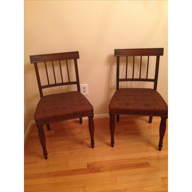 Pair of charming cherry wood side chairs. Dark brown finish with subtle wood details. Rich golden brown upholstery....