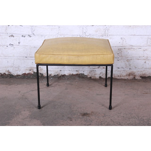 Offering a stylish mid-century modern stool or ottoman designed by Paul McCobb. The stool has nice black iron legs with...