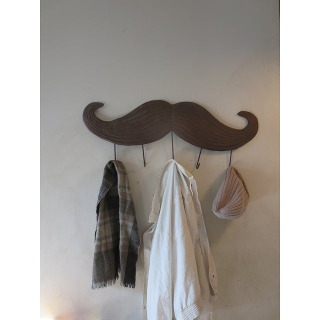 Our handmade mustache coat rack features hammered details and a rustic finish. Handmade in Haiti it bears all the...