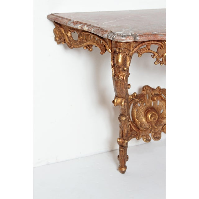 A beautiful Louis XV French 18th Century gilt wood console table with marble top. Heavily carved and pierced front apron....