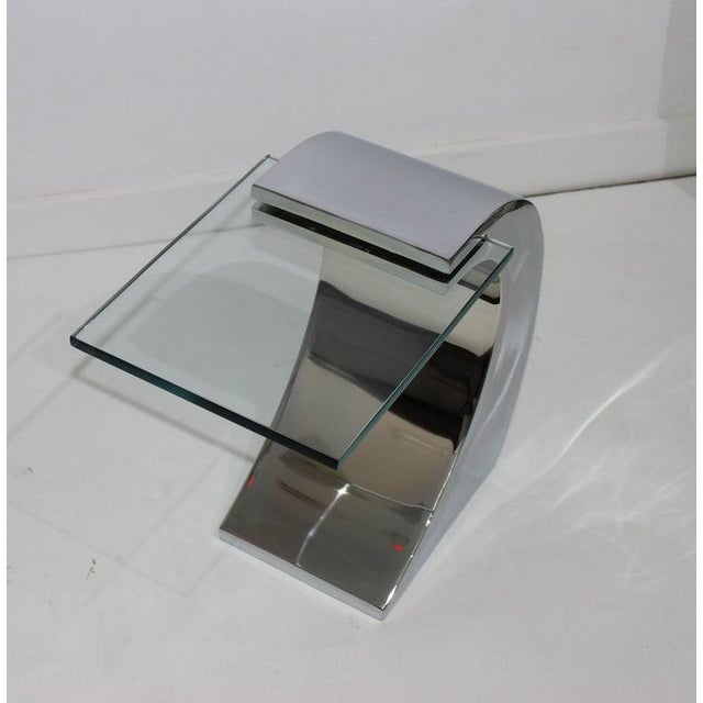 "This stylish and chic ""wave-form"" drinks table is fabricated in polished stainless steel and glass."