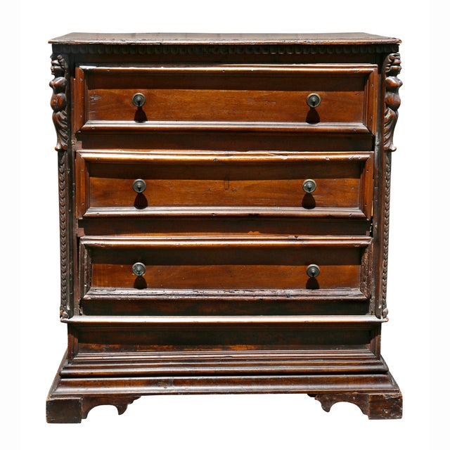 With a rectangular top over three drawers flanked by carved figures, raised on bracket feet.