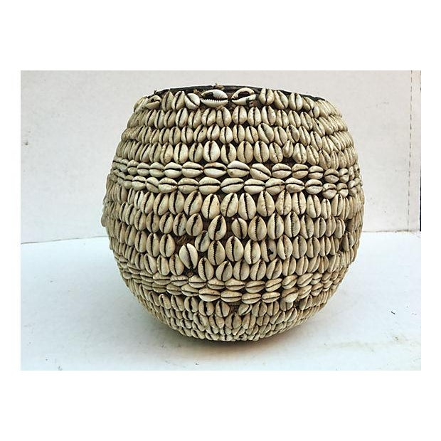 Handwoven basket decorated with shells attached to raffia with leather trim from the Nigerian Hausa tribe.