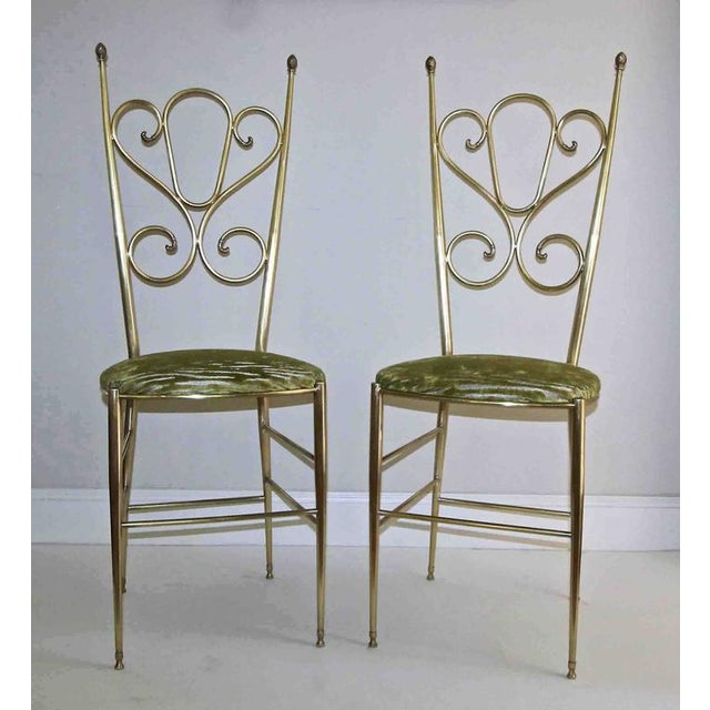 Pair of brass Italian tall back side chairs with scrolling back and pineapple finial details. Slip seats are covered in a...