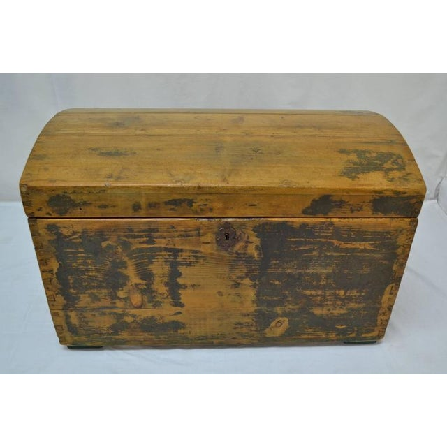 This is a sturdy little dome top trunk with exposed hand-cut dovetails on all corners, a pressed tin Baroque-style...