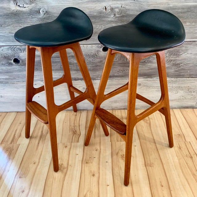Pair of iconic 1960s Danish Modern teak bar stools by Erik Buch for Oddense Maskinsnedkeri A.S. Seats are upholstered in...