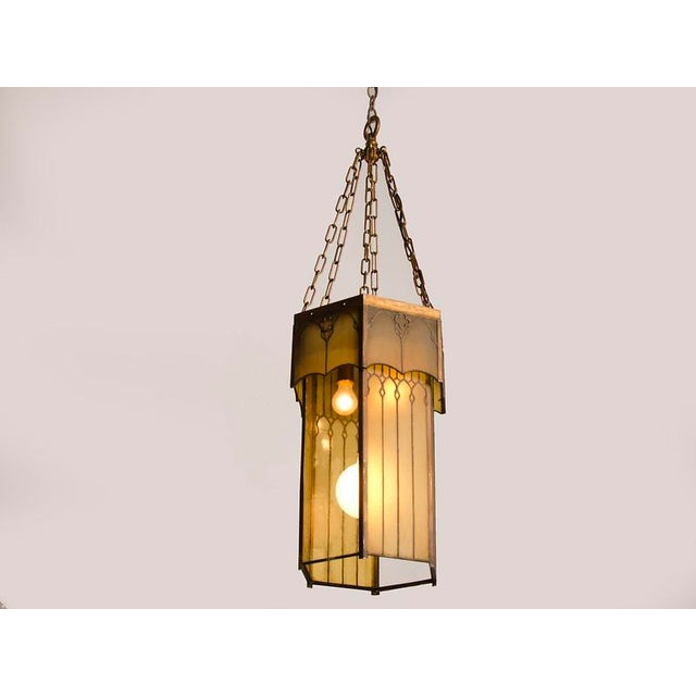 A tall and slender Arts and Crafts hexagonal lantern with an elaborate metal frame and custom coloured glass panes from...