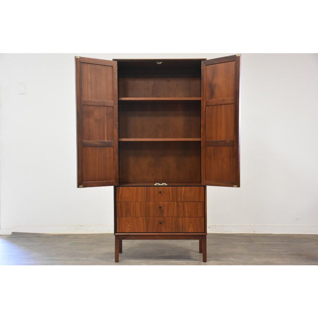 A beautiful mid century modern walnut case armoire designed by Jack Cartwright for Founders Furniture featuring two cane...