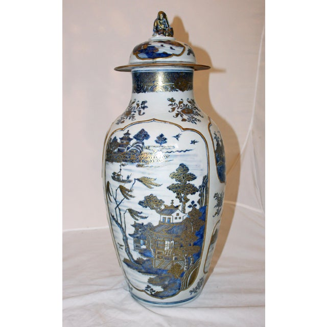 Pair of Chinese covered jars. c. 1740-80, Qing dynasty. Blue underglaze with elaborate gilding. The reserves are all...