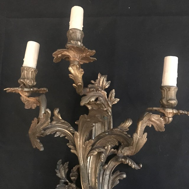 Beautiful antique pair of large French gold gilt bronze sconces, with ornate scrollwork and acanthus leaves. Rewired to US...