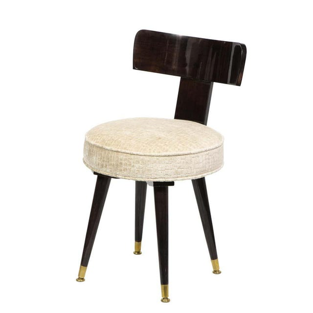 This elegant Mid-Century Modern vanity chair was realized in the United States, circa 1950. It features a subtly convex...