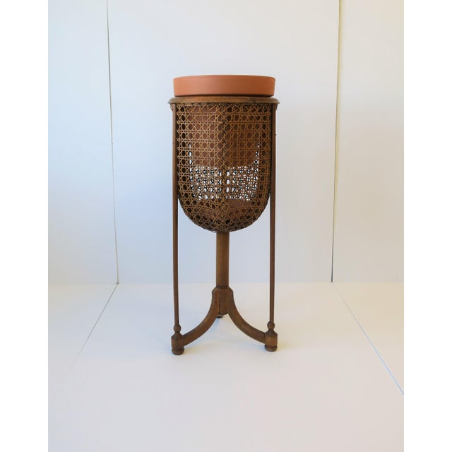 A beautiful vintage wicker cane plant stand with tri-pod base/legs, circa 1960s-1970s. Plant Stand has a beautiful round...