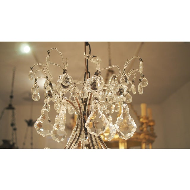 An eight light chandelier completely encrusted with crystals and tiny beads. Flexible stems extend from flowers on each...