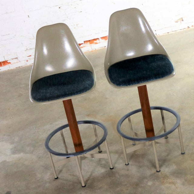 Handsome and iconic pair of mid-century modern swivel bar stools with footrest and upholstered seat pad by Burke, Inc....