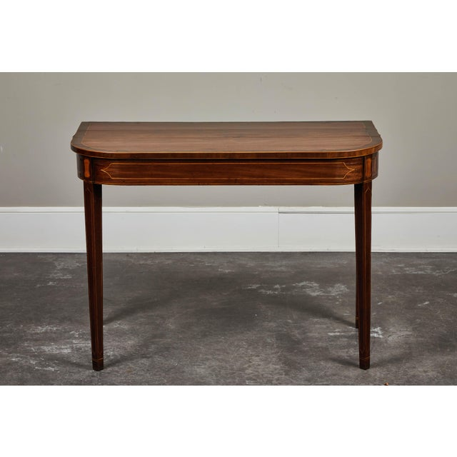 A handsome 19th century English mahogany inlaid console table featuring an inlaid squared tapered set of feet.