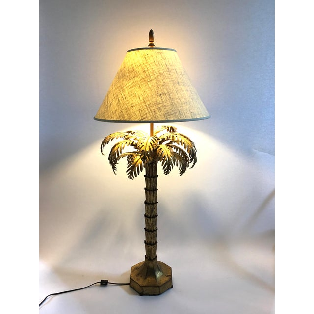 A stylish gilt metal palm tree lamp, the naturalistically modeled palm fronds issuing from the fluted tiered trunk, on an...