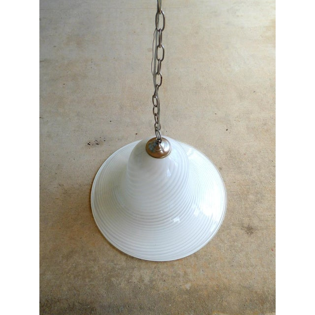 A large Murano art glass pendant attributed to Seguso. Bell form with white swirl pattern and chrome hardware. All working...