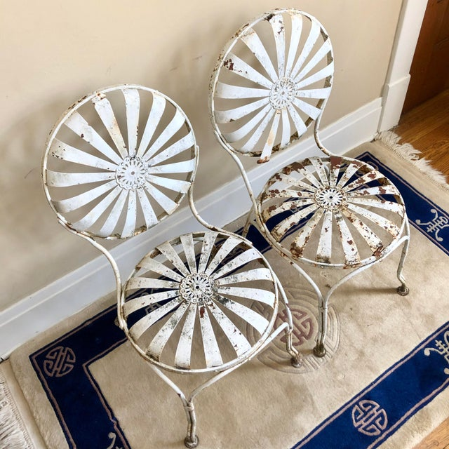 "A pair of French white iron sunburst garden chairs by Francois Carre. There is an approximately 0.5""- 1"" difference in..."
