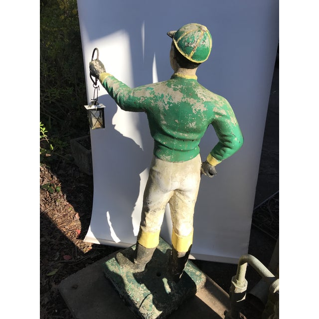 Standing concrete lawn jockey or jocko statue with extended arm and lantern. This equestrian statue graced the gardens of...
