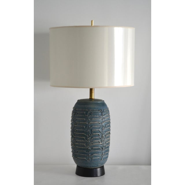 Striking Mid-Century blue glazed ceramic table lamp, circa 1950s -1960s. This stunningly textural hand thrown lamp is...