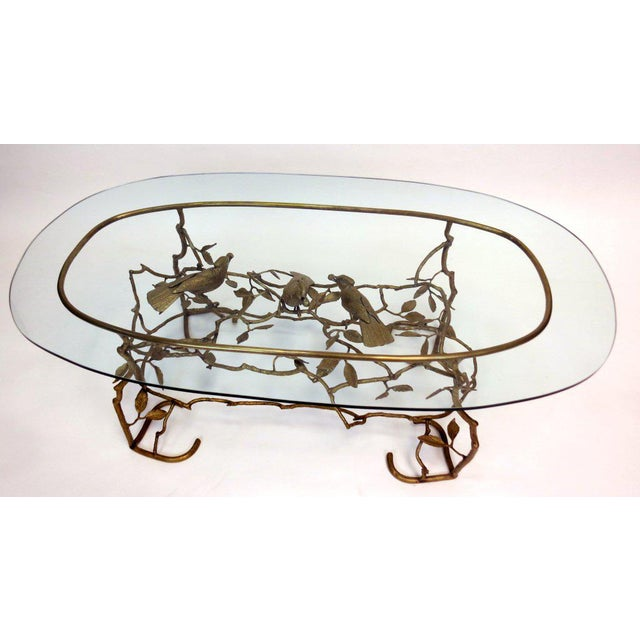 Sculptural brass coffee table with three birds in branches forming the base. Conforming oval glass top.Lovely form and...