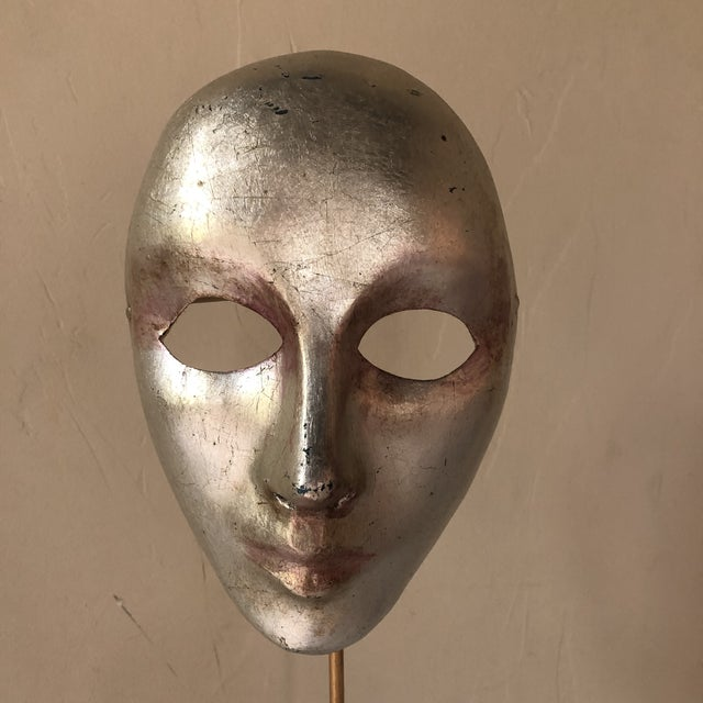 A Venetian Carnivale mask of silver-leafed paper-mâché made by Balocoloc mounted on a custom polychromed steel stand. Mask...