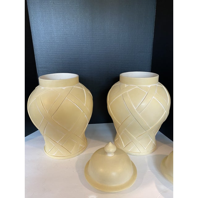 A pair of creamy white ginger jars with lattice work design were originally purchased in Neiman Marcus in the 90s.
