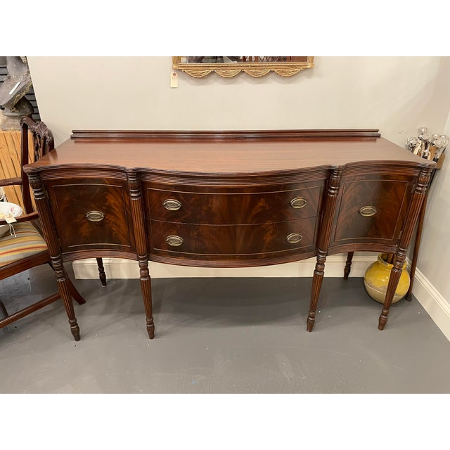 This is an absolutely beautiful vintage sideboard. It is flame mahogany with beautiful original brass hardware. The...