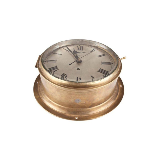 A handsome ship's clock in a brass casing with nickel face and roman numerals. Signed Viking. This is a spring mechanism...
