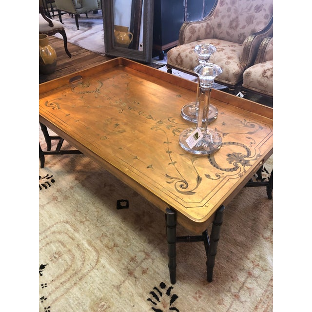A very large glamorous tray style coffee table having gilded and hand painted top with hand painted top with handles and a...