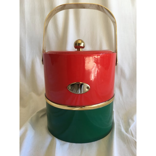 A mid-century Georges Briard ice bucket in holiday red and green colors. Vinyl sides with brass handle and finial. In...