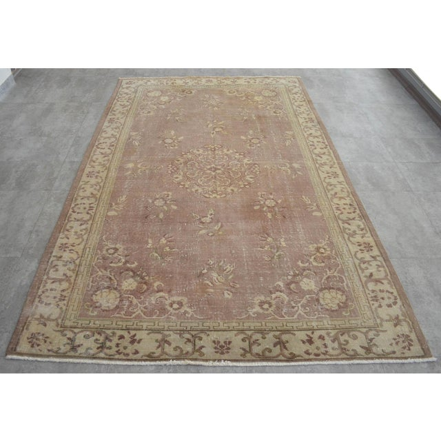 This is a beautiful vintage hand knotted distressed finish Rug from Turkey. It has sandal primary colors on an soft green...