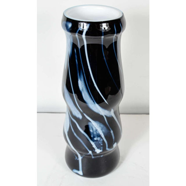 This modernist vase features a hand blown white feathered and linear glass design on a black glass background. It is...