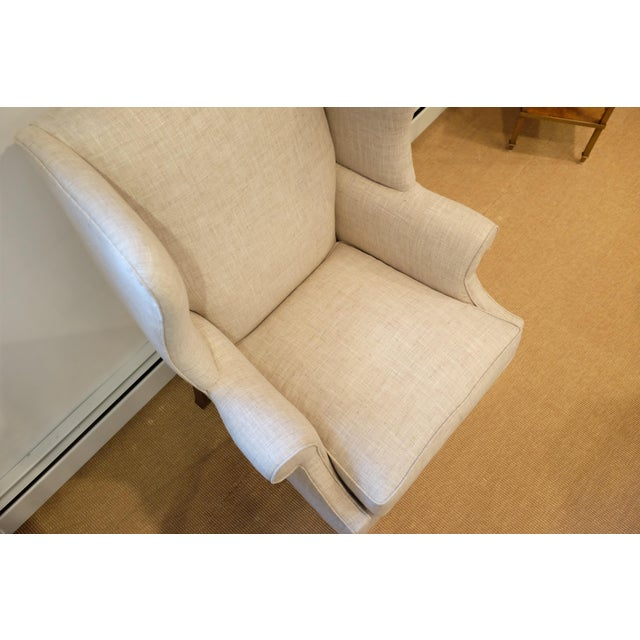Beautiful, lightly-textured wingback chair in cream colored, almost plaid-like, fabric with detailed nailhead trim along...
