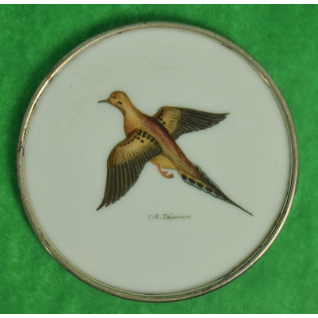 This is a set of 4 vintage coasters from the 1950s. The pieces feature game bird motifs upon milk glass with sterling...
